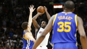 Miami Heat guard Dion Waiters, centre, goes up for a three-point shot against Golden State Warriors guard Klay Thompson, left, as forward Kevin Durant looks on during the last with 0.6 seconds of an NBA basketball game in Miami on Monday, Jan. 23, 2017. (AP / Wilfredo Lee)