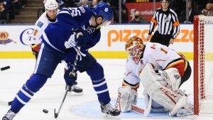 Toronto Maple Leafs left wing James van Riemsdyk takes a shot between his legs on Calgary Flames goalie Brian Elliott during second period NHL hockey action in Toronto on Monday, Jan. 23, 2017. (Nathan Denette / THE CANADIAN PRESS)
