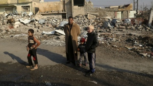 Iraqi civilians stand in front of their destroyed house in the eastern side of Mosul, Iraq, Monday, Jan. 23, 2017. (AP / Khalid Mohammed)
