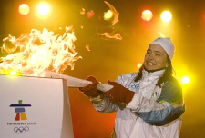 Vicky Sunohara lights the Olympic Flame in Nathan Phillips Square as the Vancouver 2010 Olympic torch relay passes through downtown Toronto on Thursday December 17, 2009. (THE CANADIAN PRESS/Chris Young)