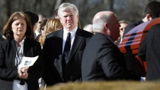 Brian Burke and his first wife Kerry, left, watch as the casket of their son Brendan is taken from the hearse into a memorial service in Canton, Mass., Tuesday, Feb. 9, 2010. (AP / Michael Dwyer)