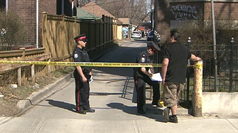 Toronto police cordone off a laneway where the body of a middle aged man was found on April 4, 2010.