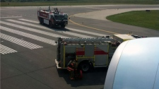 This photo taken out the plane window shows fire trucks waiting on a runway in Toronto Monday, May 28, 2012. (Photo courtesy of Jason Flick)