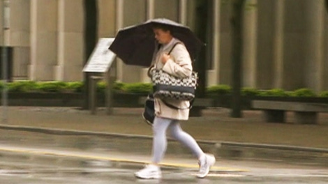 A pedestrian uses an umbrella to shield herself from the rain in Toronto on Friday, June 1, 2012.