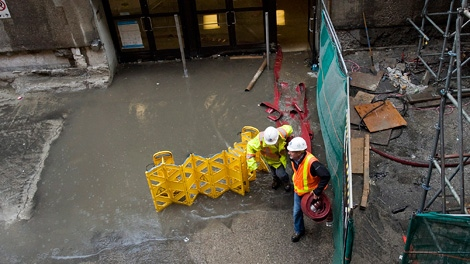 Crews work to contain water after heavy rains caused flooding in the Royal Bank Plaza and Union Station in Toronto on Friday, June 1, 2012. (Aaron Vincent Elkaim / THE CANADIAN PRESS)