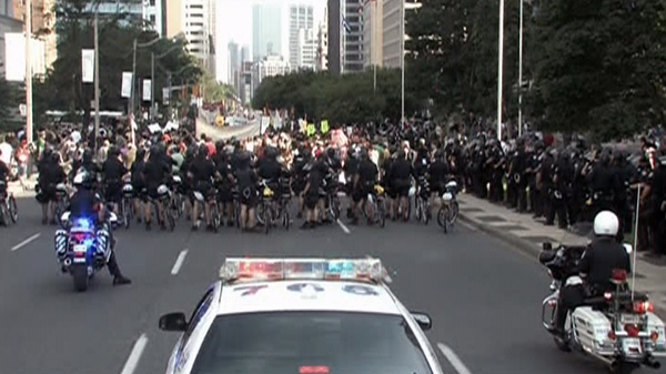 Police keep a close eye on approximately 1,000 protesters moving down University Avenue in Toronto, Friday, June 25, 2010.