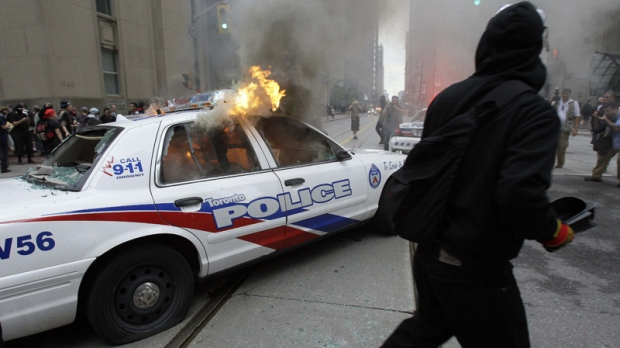 Protesters surround a burning police car at King and Bay streets during demonstrations in downtown Toronto Saturday, June 26, 2010. (AP / Gerry Broome)