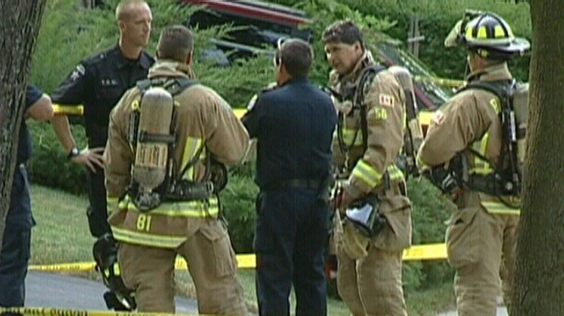 Police and firefighters investigate the scene where explosive devices were found during a search warrant in a cold case investigation on Thursday, July 12, 2012.