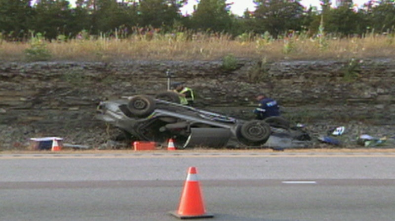 Police investigate the site of a vehicle rollover on Highway 401 near Napanee, Ont. on Saturday, July 14, 2012.