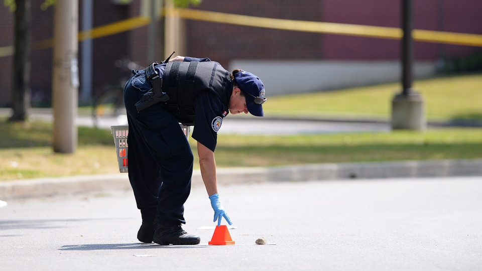 A police officer places a marker on Danzig Street in Toronto on Tuesday, July 17, 2012, near the scene of a shooting the day before. (Aaron Vincent Elkaim / THE CANADIAN PRESS)