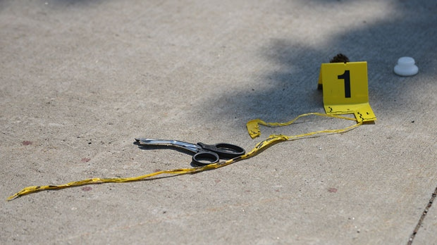 A police marker and surgical scissors lie on the ground near the scene of Monday night's shooting on Danzig Street in Toronto, Tuesday July 17, 2012. (Aaron Vincent Elkaim / THE CANADIAN PRESS)