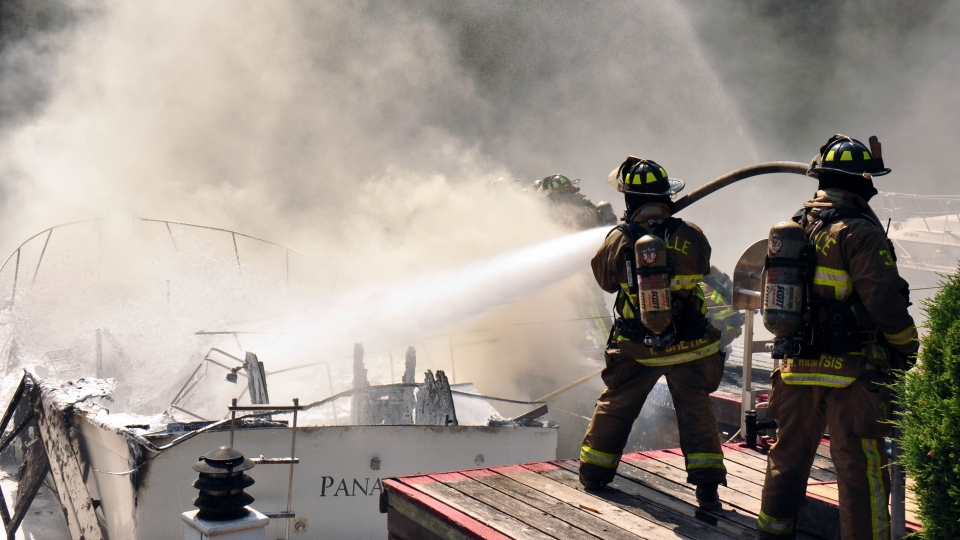 Firefighter extinguish the wreckage of a boat that exploded in Oakville on July 21, 2012. (Photo courtesy: David Ritchie)