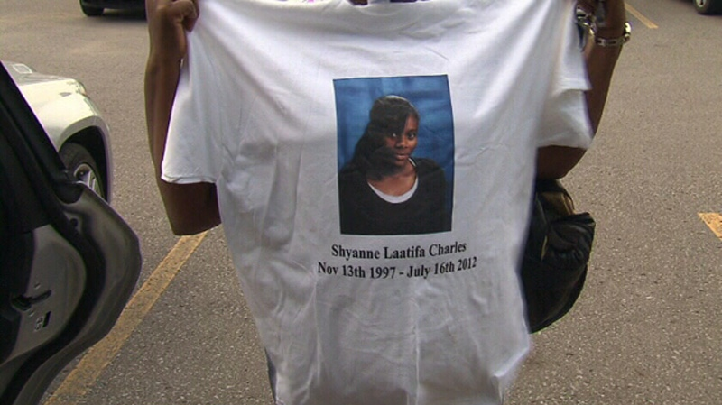 A woman who attended the visitation is seen holding a T-shirt with an image of Shyanne Charles in Toronto, Friday, July 27, 2012.