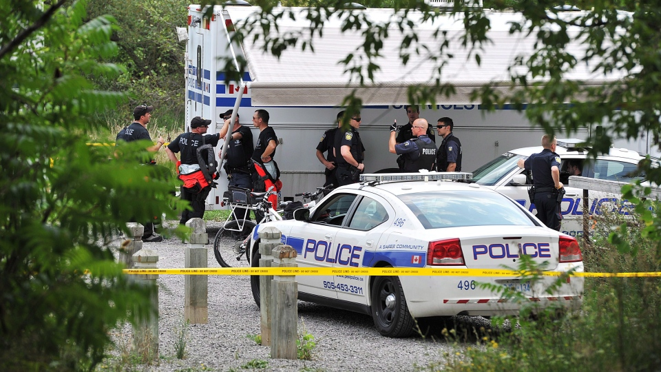 A Police team is seen in Hewick Meadows Park in Mississauga, Ont., after discovering a female severed head in the Credit River on Thursday Aug. 16, 2012. (Aaron Vincent Elkaim / THE CANADIAN PRESS)