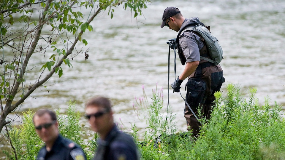 A Police search dog unit searches the banks of the Credit River in Hewick Meadows Park in Mississauga, Ont., after police discovered a female severed head on Thursday August 16, 2012. (Aaron Vincent Elkaim / THE CANADIAN PRESS)