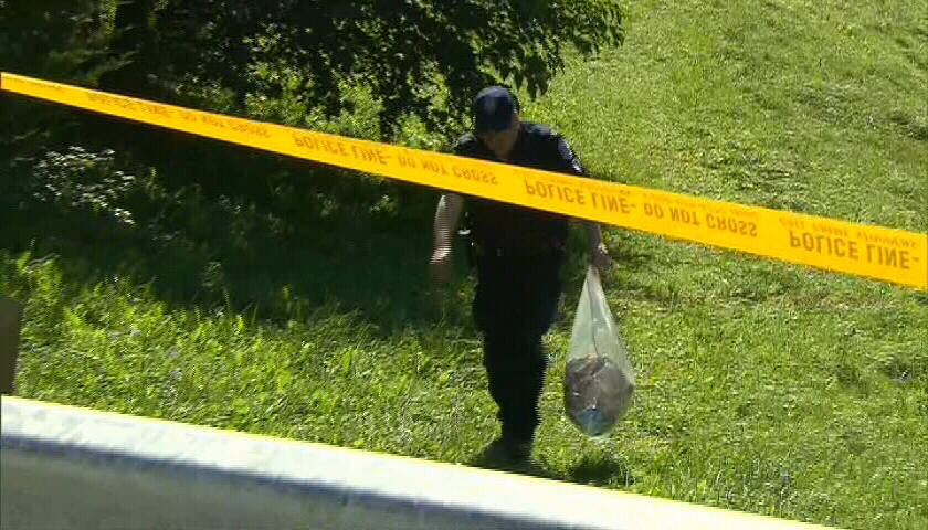 A Toronto police officer carries a bag of evidence in Scarborough, Ont., Monday, Aug. 20, 2012.