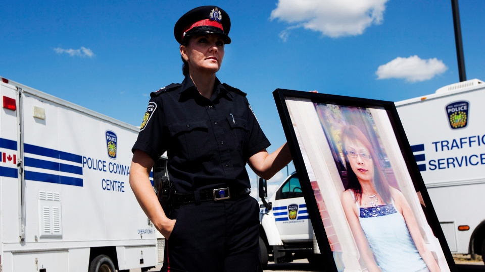 Peel Regional Police Const. Erin Cooper holds a photo of Guang Hua Liu during a press conference in Mississauga, Ont., Tuesday, Aug. 21, 2012. (Michelle Siu / THE CANADIAN PRESS)