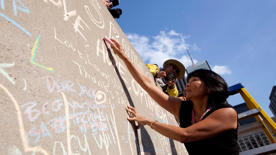 Olivia Chow writes a message on a make shift memorial wall for her husband, the late Jack Layton, as crowds gather to mark the one year anniversary of the former NDP Federal leader's passing in Toronto on Wednesday August 22 2012. THE CANADIAN PRESS/Michelle Siu