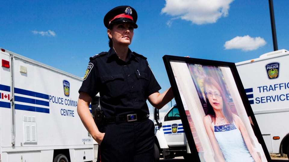 Peel Regional Police Const. Erin Cooper holds a photo during a press conference in Mississauga, Ont., Tuesday, Aug. 21, 2012. (Michelle Siu / THE CANADIAN PRESS)