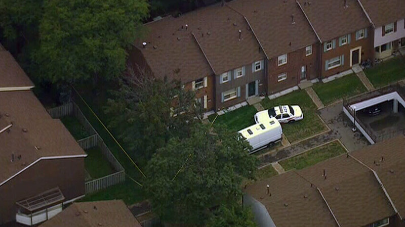 Police vehicles sit on the lawn of a townhouse complex, home to a suspect in a dismemberment case, in Toronto, Monday Aug. 27, 2012.