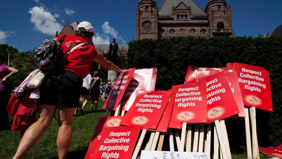 "A protester places a sign on a pile in front of Queen's Park following a rally against the ""Putting Students First Act"" that freezes Ontario Teachers' wages and cuts benefits in Toronto on Tuesday, August 28, 2012. (Michelle Siu / THE CANADIAN PRESS)"