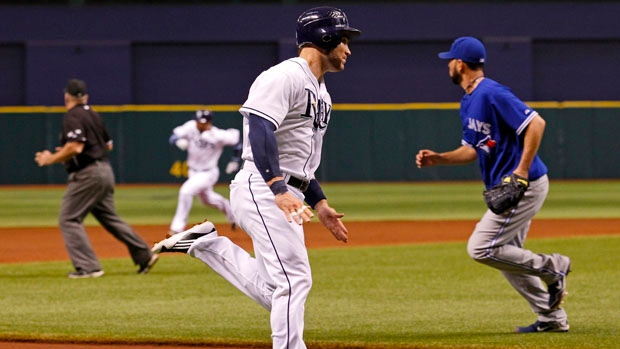 Tampa Bay Rays' Luke Scott, center, heads for home to score on a triple by Carlos Pena, in the backg