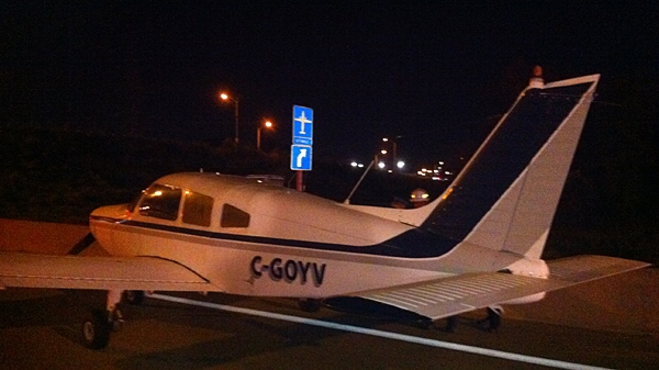 This Piper aircraft made a safe landing on Highway 407 near Woodbine Ave. late on Friday, Oct. 8, 2010. Note the sign pointing to nearby Buttonville Airport. (Tom Podolec/CTV Toronto)
